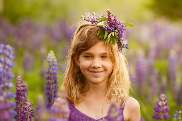 Beautiful girl smiling in a violet dress with a wreath of lupines