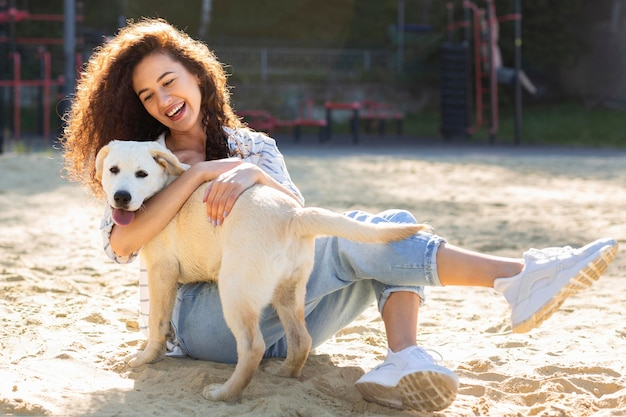Beautiful girl smiling while hugging her dog