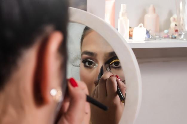 Beautiful girl smudging eye makeup for halloween in her bedroom.