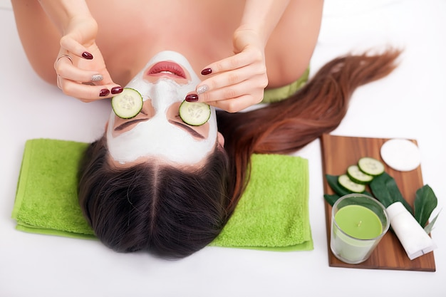 Beautiful girl at spa salon with cucumbers on eyes