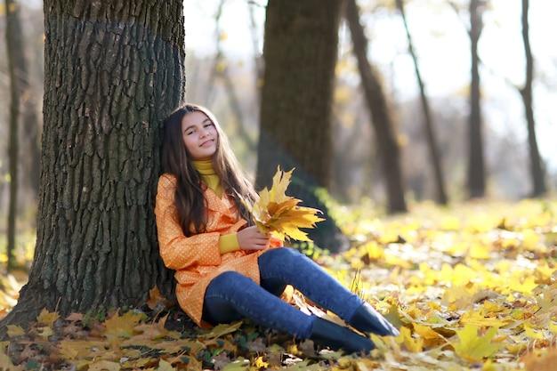 Красивая девушка проводит время в парке в осенний сезон