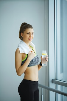Beautiful girl in sportswear with bottle of water