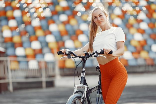 Bella ragazza allo stadio. ragazza di sport in abiti sportivi. donna con bicicletta;