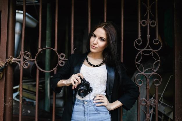 카메라와 함께 벽에 서있는 아름 다운 여자