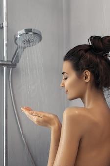 シャワーで立っている美しい少女。幸せな混血白人アジアのスリムな女性の肖像画