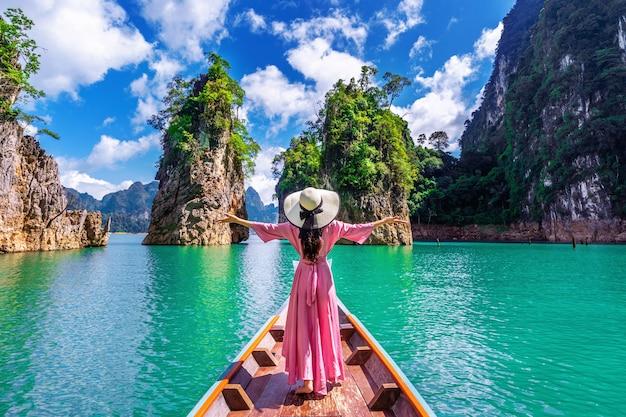 Bella ragazza in piedi sulla barca e guardando alle montagne nella diga di ratchaprapha al parco nazionale di khao sok, provincia di surat thani, thailandia.