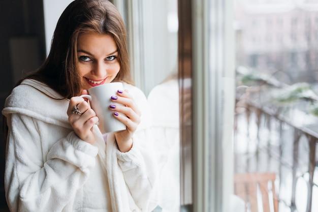 Красивая девушка, стоя у окна. она улыбается и держит в руке чашку кофе с чаем. среди мягкого утреннего солнца сквозь стеклянное окно светит.