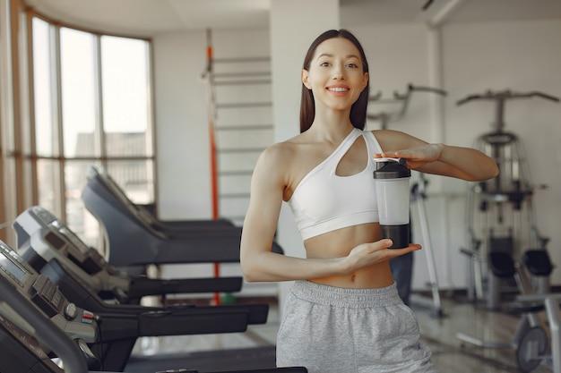 Una bella ragazza in piedi in una palestra con una bottiglia di acqua