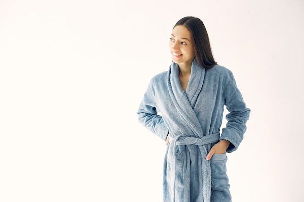 青いバスローブのスタジオで立っている美しい少女