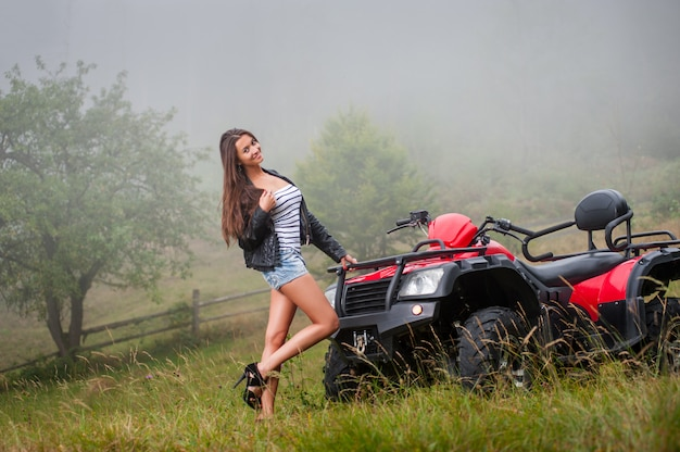 Beautiful girl standing near four-wheeler atv