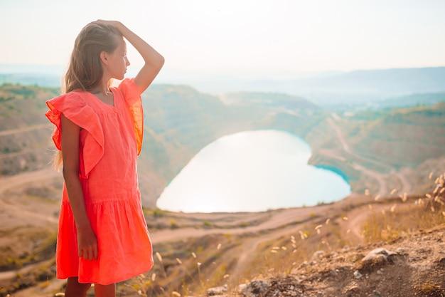 心のように湖の近くに立っている美しい少女。ヨーロッパの休暇の概念。美しい風景