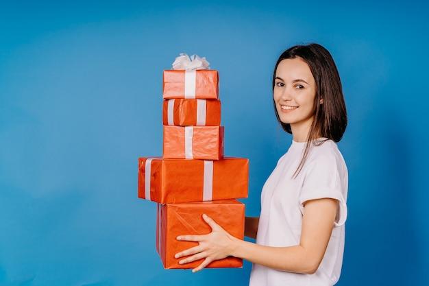 손에 선물 파란색 배경에 서있는 아름 다운 소녀는 사랑스러운 미소를 미소 짓는다. 사무실에서 크리스마스 또는 새해 축하