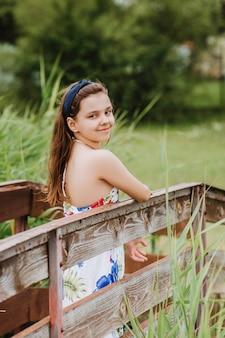 Красивая девушка стоя на деревянной пристани на берегу озера. летний отпуск