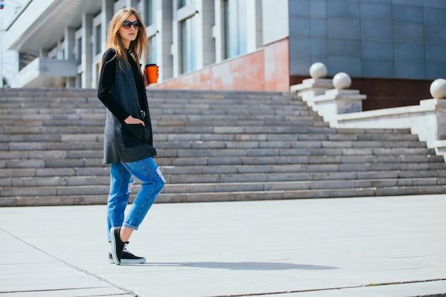Красивая девушка стоя на улице с кофе и очками.