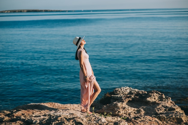 Beautiful girl standing on rocky outcrops seaside