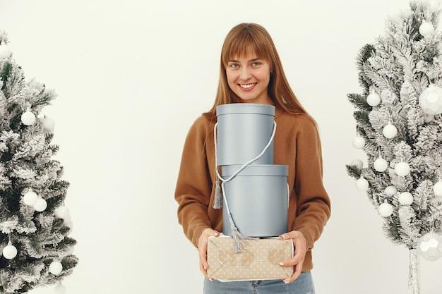 Bella ragazza in piedi in uno studio con regali