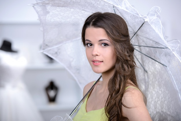 Beautiful girl standing with an umbrella in the store.