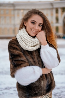 A beautiful girl stands on the background of the city christmas tree