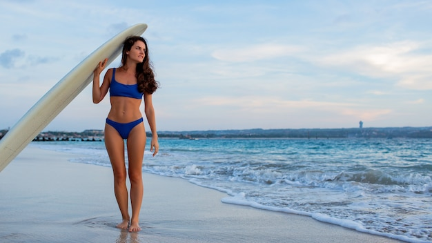 Beautiful girl stands on the beach with a surfboard.
