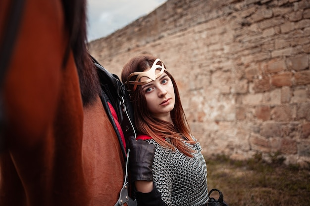 A beautiful girl stands next to a horse against a stone wall. a woman dressed as a warrior queen.