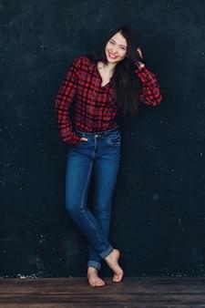 Красивая девушка стоит у стены