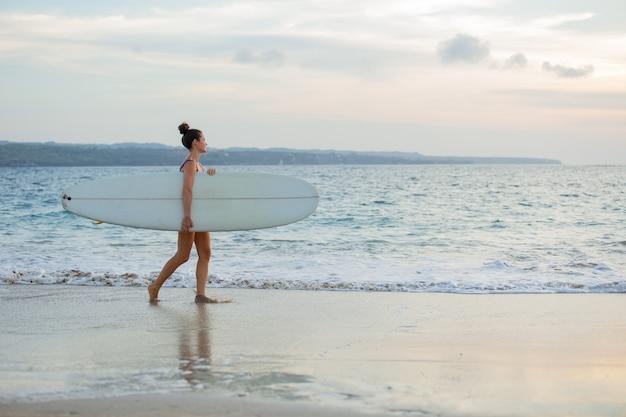 아름 다운 소녀 서핑 보드와 함께 해변에 선다.