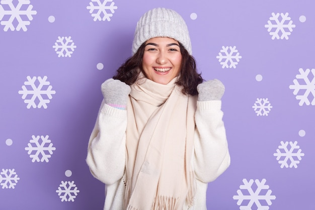 美しい少女は笑顔で立って、拳を握りしめ、成功を祝って、冬の服を着て、カメラを見て