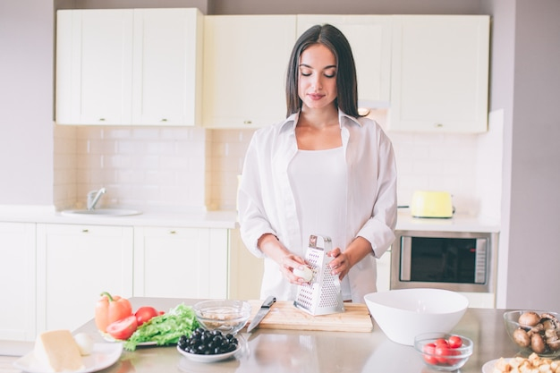 Beautiful girl stands at tabel and holds boiled egg close to grater. she looks down. girl is calm but concentrated.