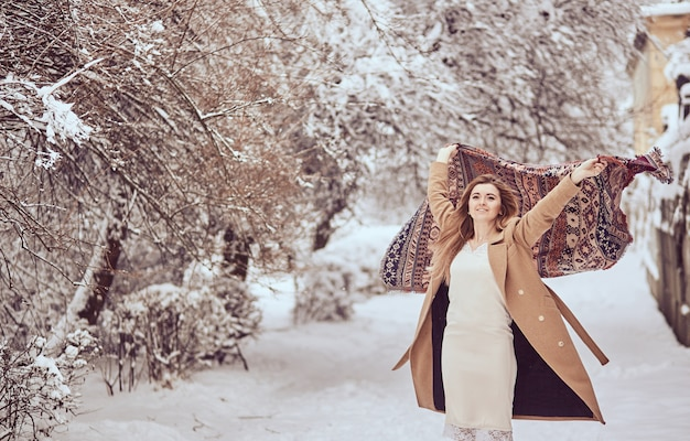 Beautiful girl stands with scarf fluttering in the wind in a winter park