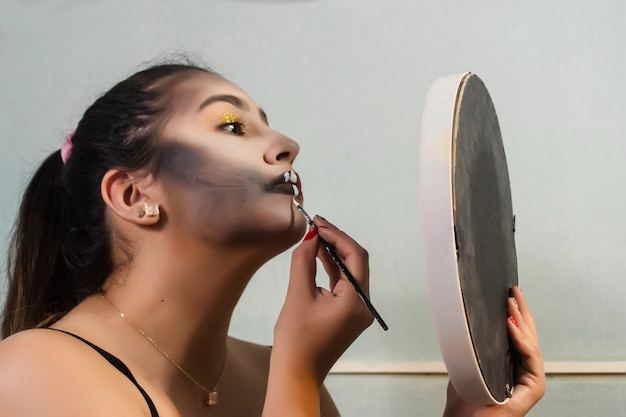 Beautiful girl starting to do her halloween themed makeup in her room.