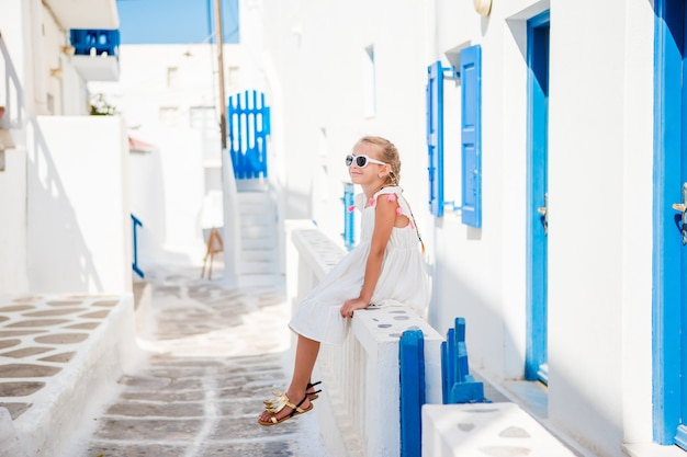 Beautiful girl at street of typical greek traditional village on mykonos