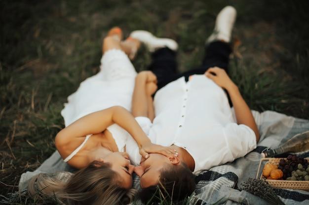 Красивая девушка гладит лицо парня на романтическом пикнике в парке, лежа на зеленой траве.