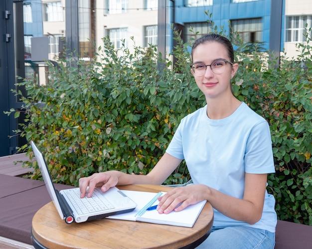 랩톱을 사용하고 메시지를 입력하고 거리에 있는 카페의 테이블에 앉아 인터넷을 검색하는 아름다운 여학생입니다. 공원에서 일하는 여학생. 비즈니스 개념입니다. 프리랜서 개념입니다.