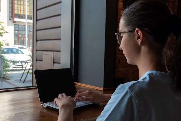 노트북을 사용하고 메시지를 입력하고 로프트 카페의 테이블에 앉아 인터넷을 검색하는 아름다운 여학생입니다. 프리랜서 개념입니다.
