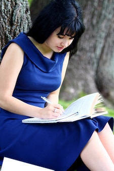 Beautiful girl studying in park
