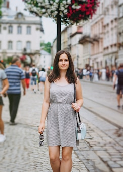 Beautiful girl in a summer dress walks the city
