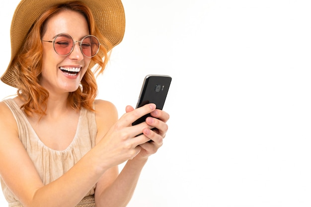 Beautiful girl in a summer hat and sunglasses takes a selfie on white with copy space