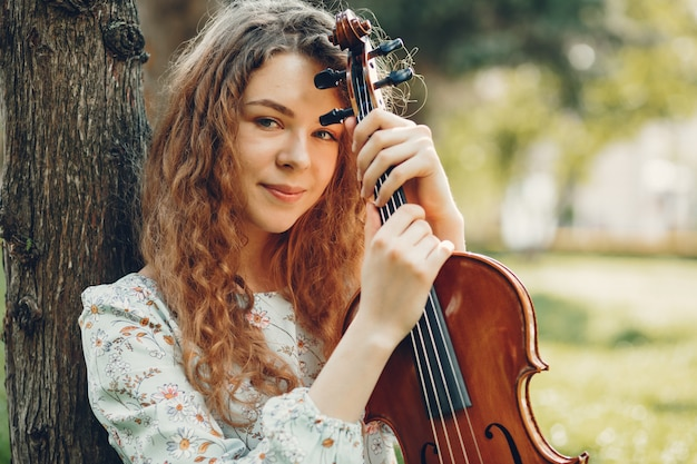 Beautiful girl in a summer park with a violin