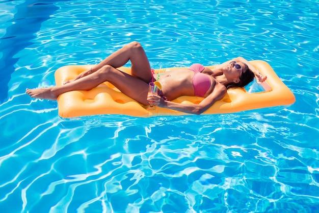 Красивая девушка загорает на надувном матрасе в бассейне