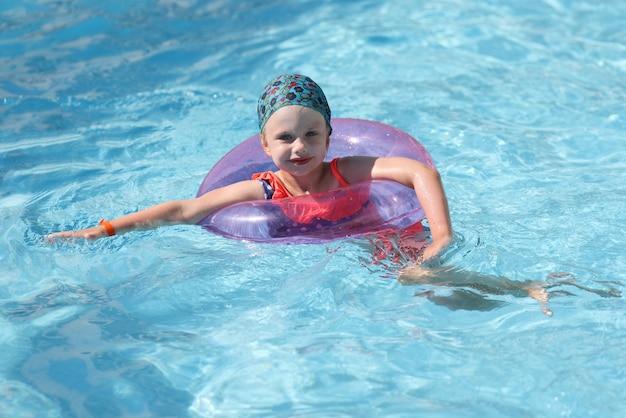 美しい少女は、インフレータブルリング付きの青いプールで泳ぐ。
