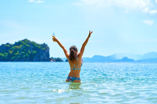 A beautiful girl in a swimsuit enjoys dancing in the ocean, holding a glass of pineapple fresh in her hand