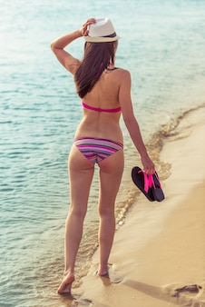 Beautiful girl in swimsuit and hat holding her flip flops.