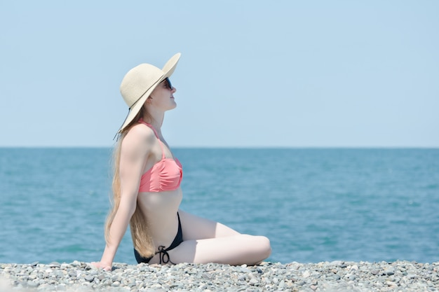 Beautiful girl in a swimsuit and hat sits on a beach on a background of the sea