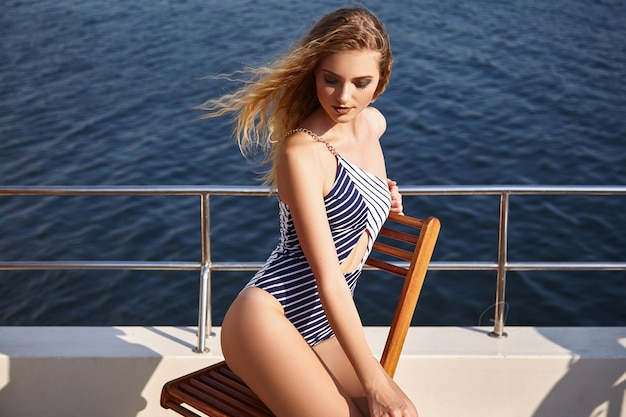 Beautiful girl in a swimsuit on a yacht