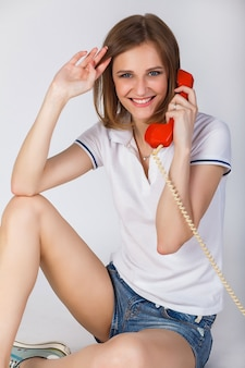 Beautiful girl in a t-shirt and denim shorts talking on a vintage red phone on the white .