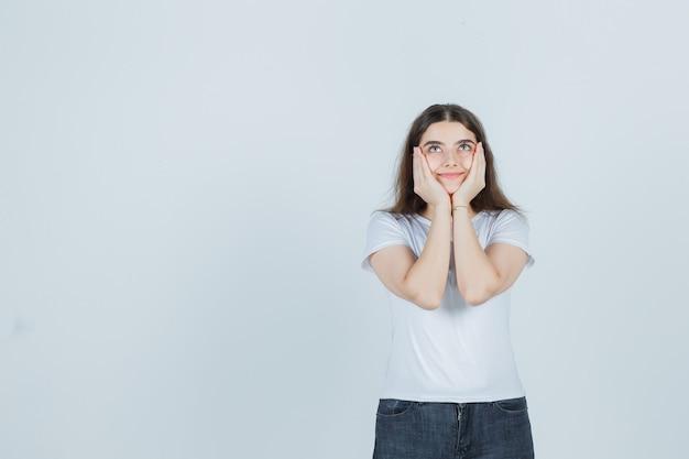 Bella ragazza in t-shirt, jeans che tengono le guance con le mani e che sembra felice, vista frontale.