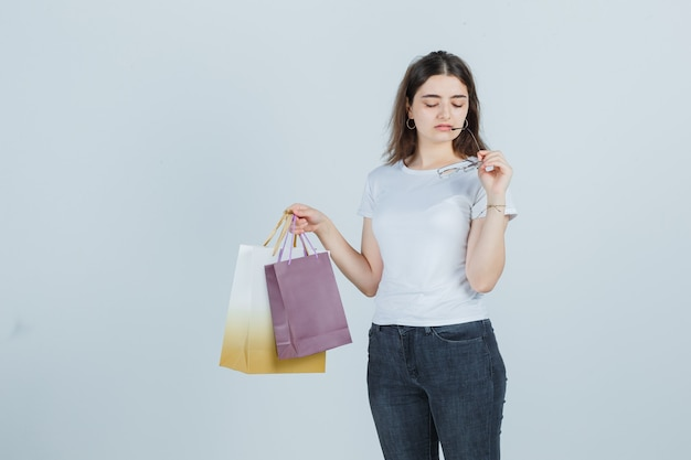 Beautiful girl in t-shirt, jeans keeping gift bags and glasses and looking sad , front view.
