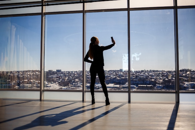 A beautiful girl takes a selfie on her phone against the background of panoramic windows in a skyscraper. selective focus
