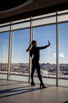 A beautiful girl takes a selfie on her phone against the background of panoramic windows in a skyscraper