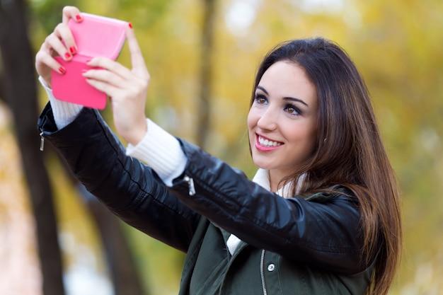 Beautiful girl taking a selfie in autumn.